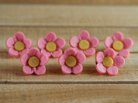 7 pink felt flowers with yellow centers lined up on a piece of real wood. Perfect for crafts or accessories.