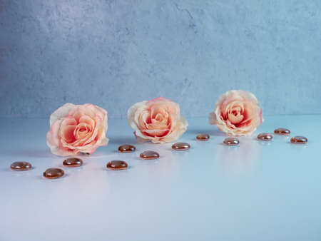 3 peach colored roses lined up with dark orange brown glass flat marbles on a white surface with a plaster background. Soft and elegant with the reflection against the white surface.