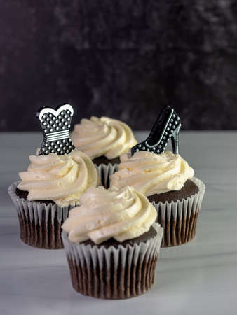 4 chocolate cupcakes with white frosting swirled high with a black and silver polka dot high heel shoe and prom dress garnishing them, on a white counter with a black marble background.
