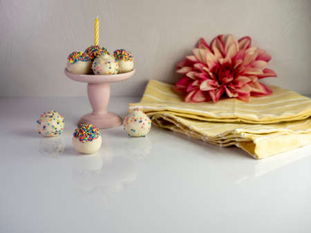 Birthday cake balls, truffle dessert, decorated with white coating and colorful sprinkles, delicious for a celebration on a white surface with a high gloss reflection.