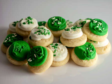 St Patrick's Day holiday frosted sugar cookies with green and white frosting and sprinkles with four leaf clover shamrocks for a festive sweet treat.