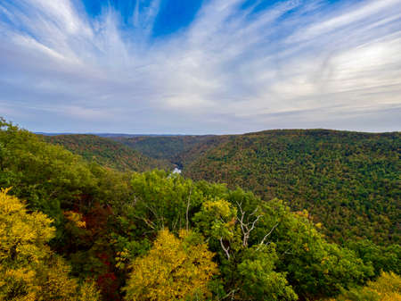 Overlook of the mountains and the fall foliage at Coopers Rock State Forest in West Virginia with the sunset golden sky one direction and a blue swirly sky the other direction, with the rock cliff.