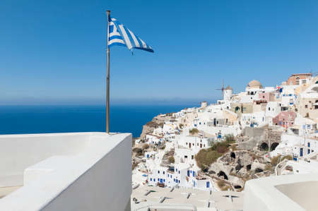 Greek Flag on pole waving in the wind. Oia, Santorini, Greece. Stock fotó - 157971265