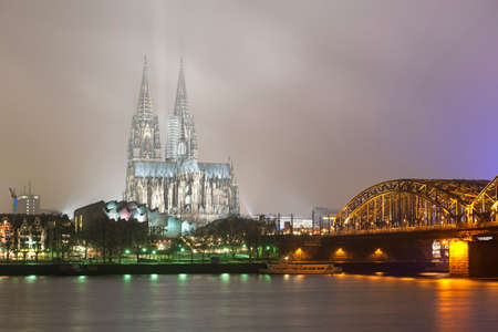 Dom (Cathedral) and railway bridge in Cologne, Germany. Rhine river in front. Foggy winter night.