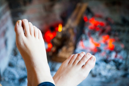 Womans feet are heated in the fire in the fireplace with a brass  photo