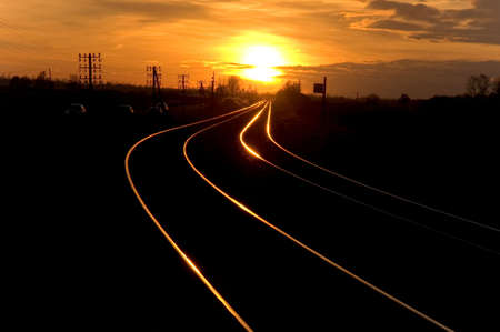 Railway with no electricity (gasol train) going to the sunset Stock Photo
