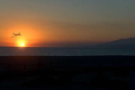 Sea a sunset or sunrise and a plane Stock Photo