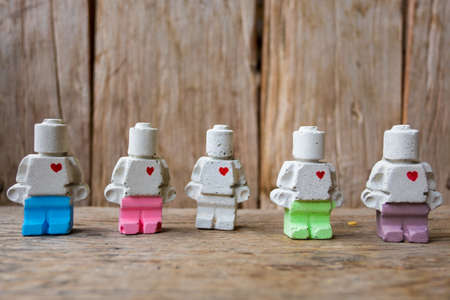 gather: Miniature clay doll standing together on wooden surface Stock Photo