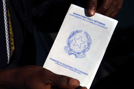 Caserta, Italy - September 27, 2019: A migrant shows his residence permit for foreigners Sajtókép