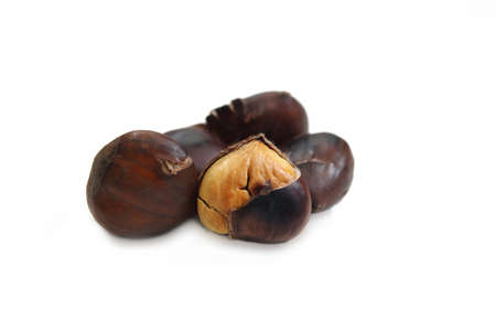 pile of cooked chestnuts with a peeled chestnut on a white background