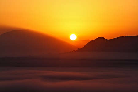 The sun rising at dawn between the mountains and the fog Archivio Fotografico