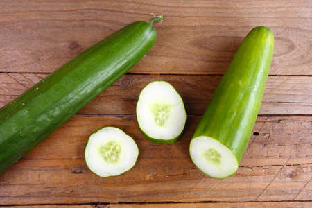 the cucumber cut into slices with the background of the wooden table Archivio Fotografico