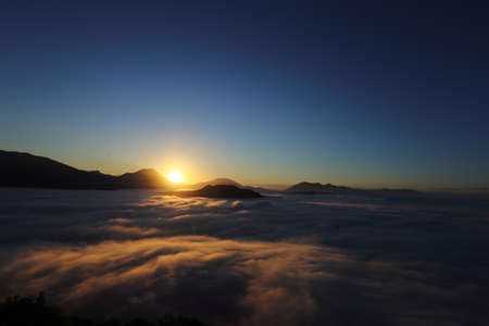 new day - the sun at dawn with fog and backlit mountains