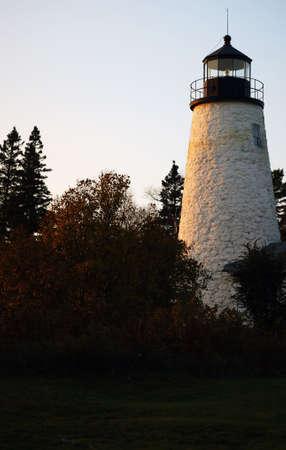 Nice sunset scene aged rock lighthouse, Castine, Maine. photo
