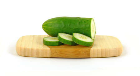 A nice view of a cucumber and slices on cutting board. photo