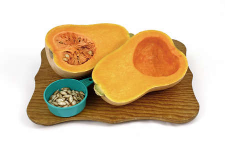 dry cleaned: Sliced butternut squash and seeds on a cutting board.