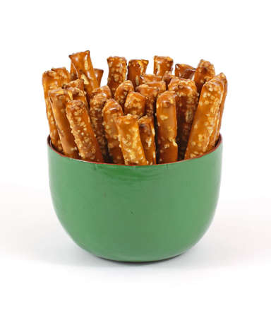 Glazed large salted stick pretzels in a green bowl. photo