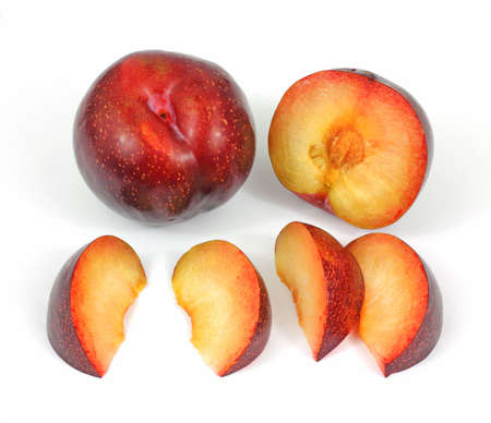 seeping: A whole and sliced tree ripened red plums.