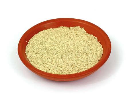 levadura: Un taz�n de cer�mica peque�as de levadura seca activa.  Foto de archivo