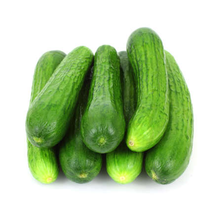 tapering: A group of small seedless cucumbers stacked.
