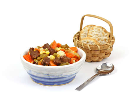 A bowl of canned vegetable beef soup crackers and spoon. photo