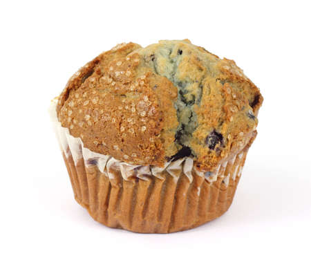 A great view of a whole freshly baked blueberry muffin.  photo
