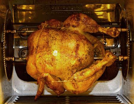 pollo rostizado: A whole fresh chicken roasting in the rotisserie. Foto de archivo