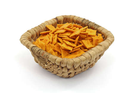 Small square cheese crackers in a woven basket. photo