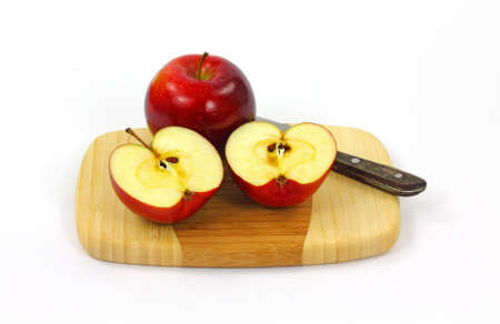 A whole and sliced Rome apple on a cutting board. photo