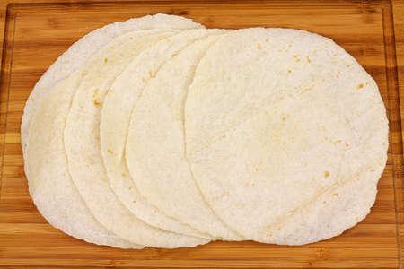 Six soft flour tortillas on a cutting board. photo