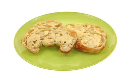 buttered: A sliced buttered cruissant on a green plate.