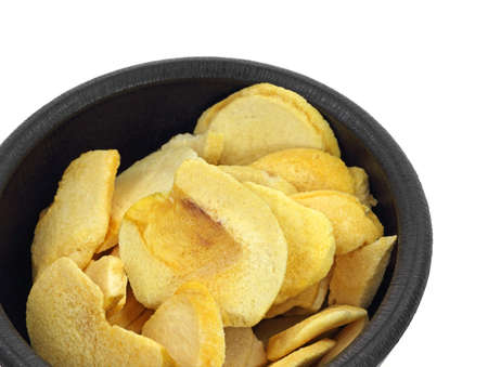 An overhead view of dried peach slices in black bowl. photo
