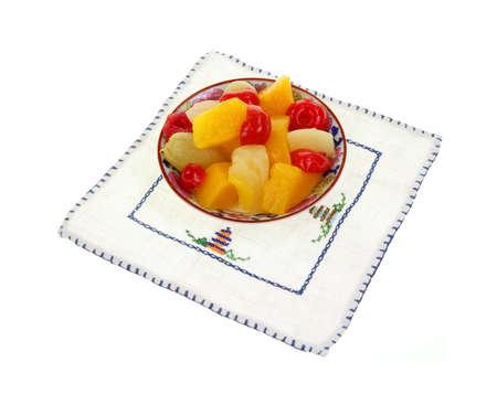 frutta sciroppata: Un piccolo piatto di frutta in scatola su una stuoia di lino ricamato delicato Archivio Fotografico
