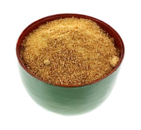 A bowl filled with coconut palm sugar granules  photo