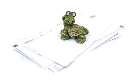 moulded: Un peque�o pisapapeles s�lido moldeado fuerte tortuga sentado en una pila de facturas pagadas