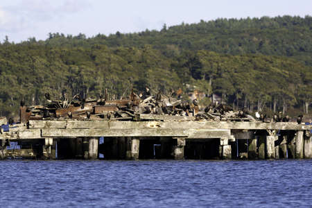 residue: Birds perched on building residue stored on a wooden  wharf on pilings in Sandy River, Maine  Stock Photo