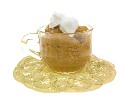 A side view of a small cup of butterscotch pudding with a dab of whip cream  Stock Photo - 17122467