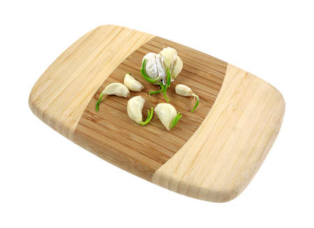 A group of separated garlic cloves on cutting board. photo