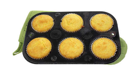 corn meal: Six corn meal muffins in baking tin cooling on mit