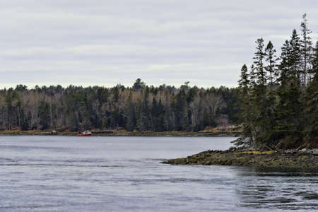 lobster boat: A red lobster boat anchored off shore across bay.