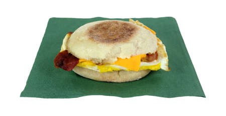 A grilled bacon egg and cheese sandwich on green napkin. photo