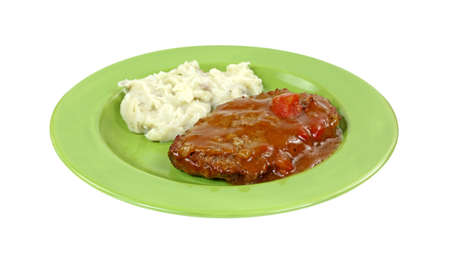 A meatloaf patty with gravy and mashed potatoes on a green plate. Stock Photo - 24027123