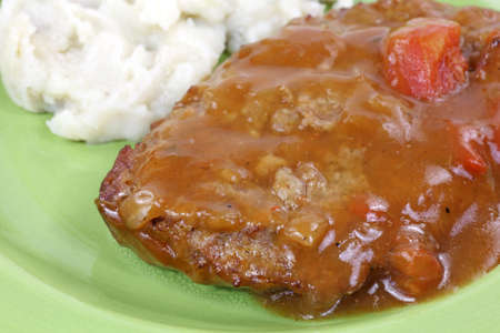 A close  view of meatloaf patty with tomato and gravy and red skin mashed potatoes on a green plate. photo