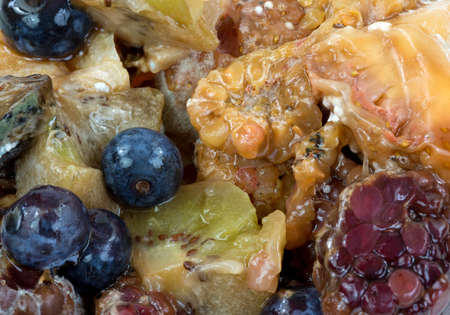 A close view of a group of rotten blackberry, raspberry, blueberry, kiwi, strawberry, and orange fruit. photo