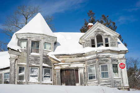 eyesore: An abandoned and ramshakle house covered with snow. Editorial