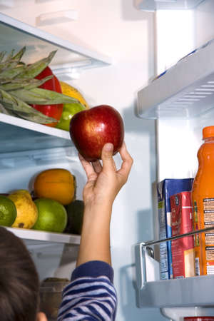 child taking the apple from the refrigerator photo