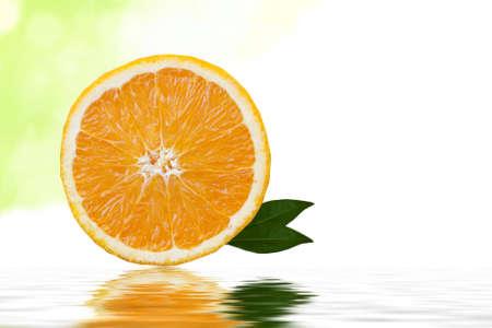rodaja de naranja sobre fondo blanco con hojas verdes photo