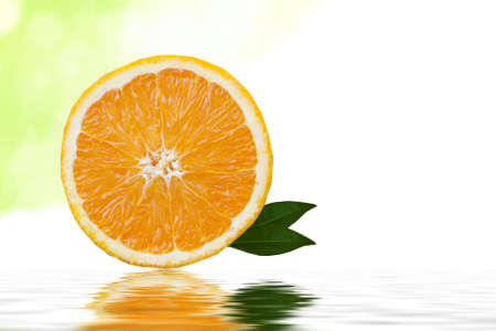 agricultura: rodaja de naranja sobre fondo blanco con hojas verdes