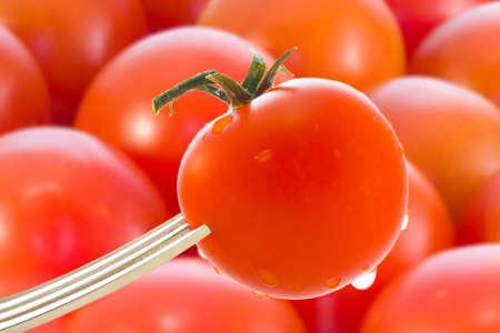 tomates con un tenedor en el primer plano de fondo y los tomates Stock Photo