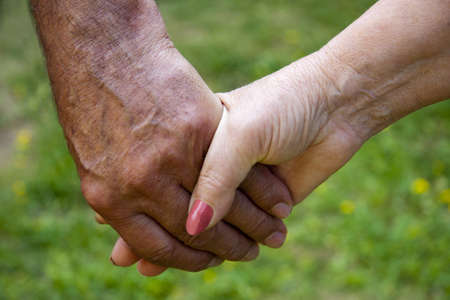 clasped hands of adults, seniors, golden age Stock Photo
